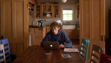 Teenage boy sitting at a kitchen table with a laptop