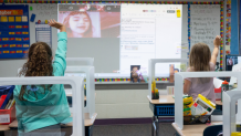 Students in a classroom wave to their online classmates