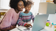 Photo of a mother and daughter looking at a laptop.