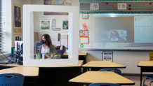 Photo of a teacher wearing a mask and using a computer