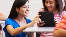 A female teacher helping a student working on a tablet in a classroom.