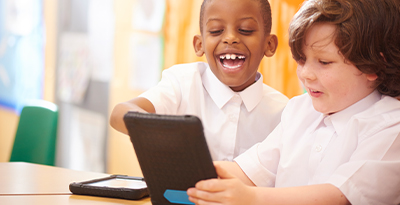 Two primary school children collaborating on a class assignment using a laptop