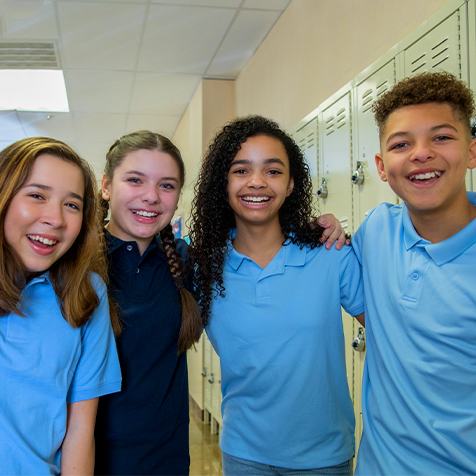 Groups of four secondary school students smiling at the camera.